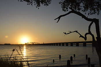 Biloxi, MS sunset view with water and bridge