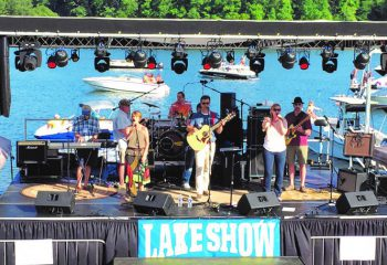 Musicians performing on an outdoor stage overlooking Lake Lanier, from previous Lake Show concert