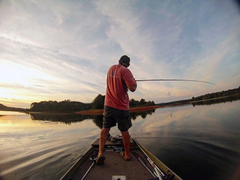Man standing on boat fishing