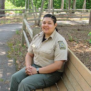New Don Carter State Park Naturalist, Vianca Milian, sitting on park bench