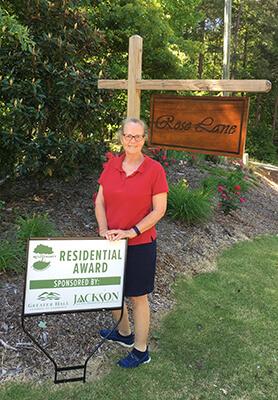 Pam Keene, Master gardener in front of Beautification award sign