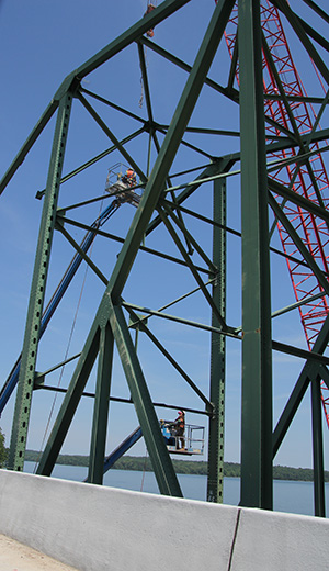 Workers high over Lake Lanier removing green trusses of Browns Bridge
