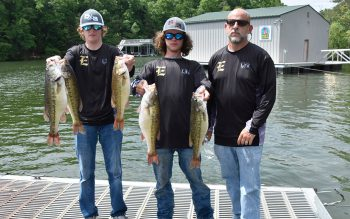High schoolers Davis Madden, Fisher Faulkner, and coach William Hopkins, pose with their catch of five spotted bass.