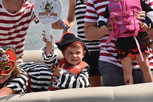 Child on boat in pirate outfit at previous Poker Run event on Lake Lanier