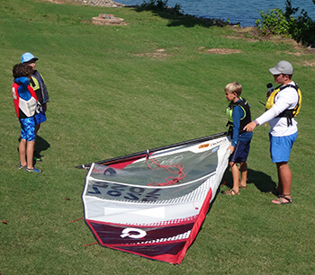 Sailing instructor pointing at sail laid out on the grass as he teaches students the parts of a sail