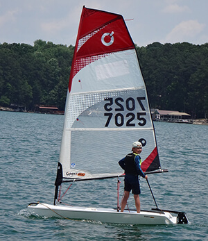 UYC Junior Sailing student standing on an Open BIC sailboat