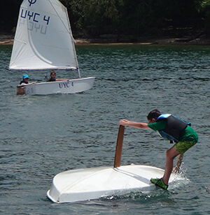 UYC Junior Sailing student trying to right sailboat by its keel