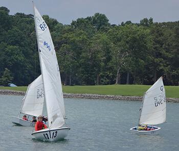 3 small sailboats with junior sailing students learning to sail on Lake Lanier