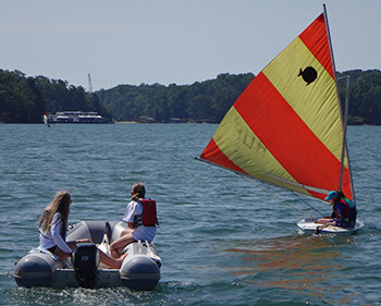 Two sailing coaches in a Zodiac provide support for junior sailing students in small sunfish sailboat