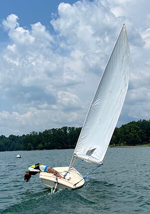 UYC Junior Sailing student hanging off side of sailboat to balance it in the wind