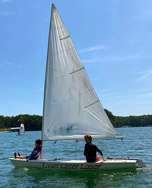 2 UYC Junior Sailing students learning to sail, one resting back against the mast, the other at the tiller.