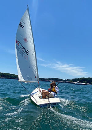 UYC Junior Sailing student aboard sailboat gets instructions from coach on how to handle the tiller.