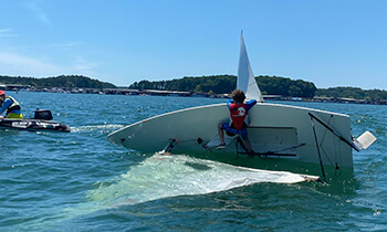 Sailing student practices righting a capsized sailboat