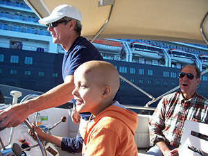 Child steering boat with help from adults at Freedom Boat Foundation event