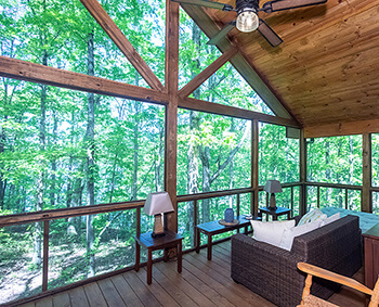 A remodeled enclosed deck area with wooden floors, wood ceiling, ceiling fan, and large windows