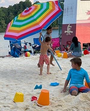 child putting up beach umbrella