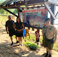 Eagle Scout candidate in front of life-jacket station