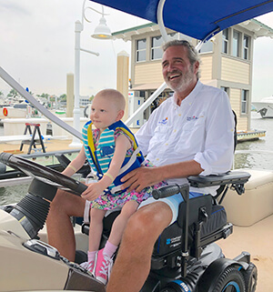 The Late Mike Donahue in wheel chair holding cancer patient as they prepare to ride in a boat