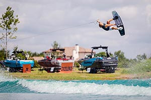 Wakeboarder in the air over lake