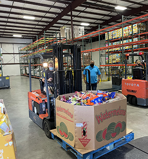 A forklift with box of food inside warehouse.