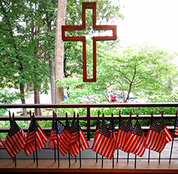 Hanging cross with American flags on table during a Memorial Day celebration