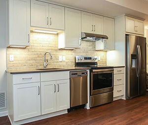 new white kitchen cabinets with overhead lighting and appliances