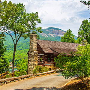view of road with stone fireplace and cabin with mountain in background