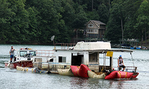 """""""The Beast"""" houseboat being floated across the lake"""