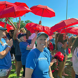 Vicki Bunke and other supporters with signature red umbrellas